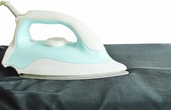 Automatic electric iron pressing black slacks on ironing board. Blue automatic electric iron pressing black slacks on ironing board Royalty Free Stock Photo