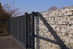 Gabion. Automatic entrance gate used in combination with a wall made of gabion stock image