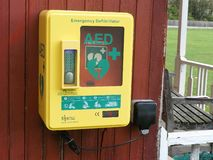 Automatic External Defibrillator AED steel unit mounted to outside wooden wall royalty free stock photo