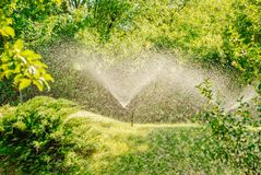 Automatic Garden Lawn sprinkler in action watering grass. Automatic Garden Lawn sprinkler in action stock photos