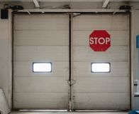 Automatic gates inside industrial storage warehouse with red stop sign stock photos