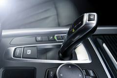 Automatic gear stick transmission of a modern car, multimedia and navigation control buttons. Car interior details. Transmission. Shift. Soft lighting stock images