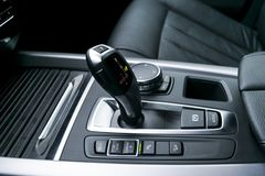 Automatic gear stick transmission of a modern car, multimedia and navigation control buttons. Car interior details. Transmission Stock Photos