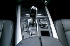 Automatic gear stick transmission of a modern car, multimedia and navigation control buttons. Car interior details. Transmission Stock Images