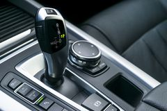Automatic gear stick transmission of a modern car, multimedia and navigation control buttons. Car interior details. Transmission. Shift royalty free stock photography