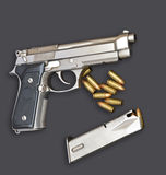 Automatic handgun pistol with magazine and bullets on gray background Royalty Free Stock Photo