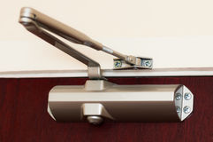 Automatic hydraulic leaver hinge door closer holder. Metallic royalty free stock photo