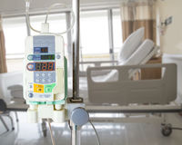 Automatic infusion pump and IV hanging on pole in hospital Stock Photo
