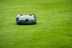 Automatic Lawn Mower. Robot mowing grass in garden, front view, selective focus royalty free stock photo