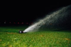 Automatic lawn sprinkler spraying water over golf course green grass. At night Stock Photos