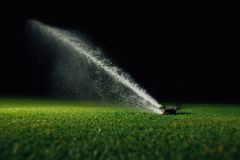 Automatic lawn sprinkler spraying water over golf course green grass. At night Royalty Free Stock Photos