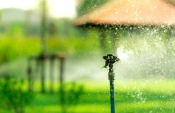 Automatic lawn sprinkler watering green grass. Sprinkler with automatic system. Garden irrigation system watering lawn. Water stock images