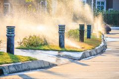 Automatic lawn sprinklers watering over green grass stock images