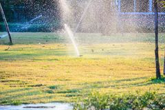 Automatic lawn sprinklers watering over green grass stock photo
