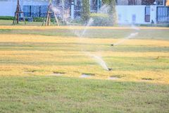 Automatic lawn sprinklers watering over green grass royalty free stock image