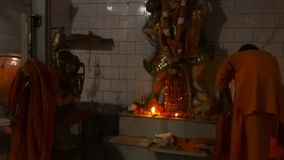 automatic machine for Aarti works monk performed ceremony light near statue of Hanuman monkey God