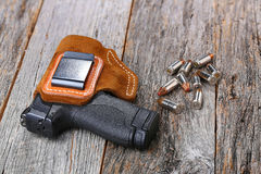 Automatic 9mm handgun. Automatic Handgun with leather holster and bullets on a wooden background Royalty Free Stock Photography