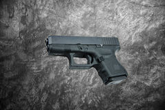 Automatic 9mm. handgun pistol on cement wall background Stock Photos