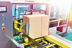 Automatic molder of cardboard boxes stock image