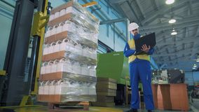 Automatic packaging of plastic canisters under male engineer`s supervision stock video