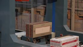 Automatic packing of products in boxes on the conveyor, close-up, packing of ceramic tiles, conveyor, modern factory. Automatic packing of production in boxes on stock footage