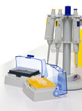 Automatic pipettes and tips, isolated. Automatic micropipettes on holder and two boxes of disposable plastic tips Stock Photos