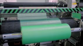 Automatic plastic bag making machine - roller with green polyethylene film. Part of automatic plastic bag making machine - moving roller with flat polyethylene stock footage