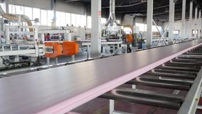 Automatic process production of building material at factory with large windows and modern machine-tool