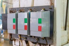 Automatic push-button switches of network equipment of three-phase network installed on the wall in the scientific and industrial royalty free stock photos