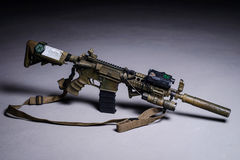 Automatic rifle with silencer and laser sight. Painted assault automatic rifle with silencer, laser sight and tactical flashlight royalty free stock images