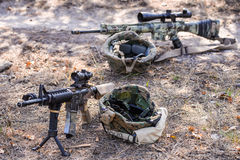 Automatic rifles with a telescopic sight. Two sniper rifles with optical sights and helmets lying on the sand in the forest royalty free stock photography