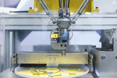 Automatic robot arm working in industrial environment sorting out screws stock photos