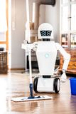 Automatic robot floor scrubber is doing his work. In an living room, vertical shot with copyspace stock photography