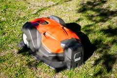 Automatic robotic lawnmower charging. A professional automatic robotic lawnmower on a charging station on green lawn Stock Photo