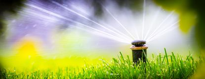 Automatic sprinkler system watering the lawn. On a background of green grass, close-up stock images