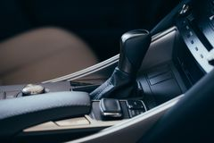 Selector automatic transmission with perforated leather in the interior of a modern expensive car. The background is blurred stock photos