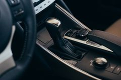 Selector automatic transmission with perforated leather in the interior of a modern expensive car. The background is blurred stock images
