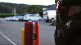 Automatic trunk opening. A man puts bright suitcases in the car. Slow motion stock video