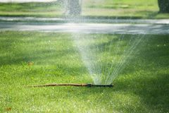 Automatic Watering the green lawn garden sprinkler on a sunny su. Mmer royalty free stock photos