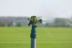 Automatic watering spout spraying Royalty Free Stock Image