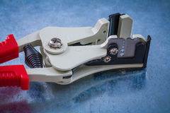 Automatic wire strippers on scratched metallic surface construct Stock Images