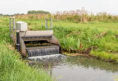 Automatic working small weir controls the water in a Dutch polde. Automatic working small galvanized iron weir controls the water in a Dutch polder. The falling stock images