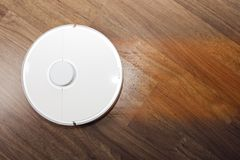 Automation cleaning. White robot vacuum cleaner. Collects dust, hair, washes the floor at home