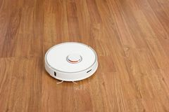 Automation cleaning. White robot vacuum cleaner stock photos