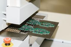 Automation of machine assembly of computer circuit board in the factory for the production of computer components. The. Process of soldering the board. Factory Stock Photography