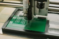 Automation of machine assembly of computer circuit board in the factory for the production of computer components. The. Process of soldering the board. Factory Stock Photo