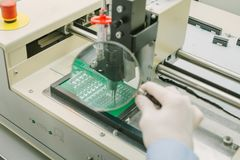 Automation of machine assembly of computer circuit board in the factory for the production of computer components. The. Process of soldering the board. Factory Royalty Free Stock Photography