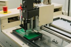 Automation of machine assembly of computer circuit board in the factory for the production of computer components. The. Process of soldering the board. Factory Stock Image