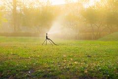 Automatische Berieselungsanlage, die auf Rasenfläche wässert Lizenzfreie Stockfotos