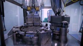 Automatische Fertigungsstraße an einem pharmazeutischen Unternehmen Die Maschine füllt die Kapsel mit Inhalt stock video footage